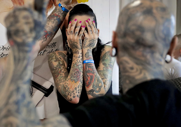 In this picture taken on Sunday, Oct. 16, 2016, a a woman covers her face during the International Tattoo Convention Bucharest 2016 in Bucharest, Romania. More than 100 tattoo and piercing artists brought their skills and art to a three-day convention in the Romanian capital.(AP Photo/Vadim Ghirda)