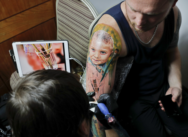 In this picture taken on Sunday, Oct. 16, 2016, Serghei, from the Republic of Moldova, gets a tattoo showing his son Chiril applied to his hand, during the International Tattoo Convention Bucharest 2016 in Bucharest, Romania. (AP Photo/Vadim Ghirda)