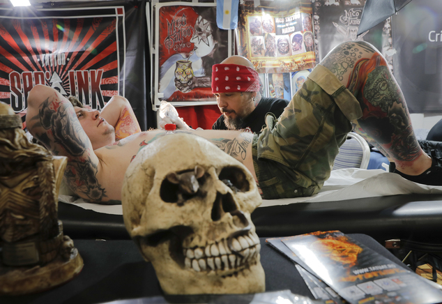 In this picture taken on Sunday, Oct. 16, 2016, a man gets a tattoo during the International Tattoo Convention Bucharest 2016 in Bucharest, Romania. More than 100 tattoo and piercing artists brought their skills and art to a three-day convention in the Romanian capital.(AP Photo/Vadim Ghirda)