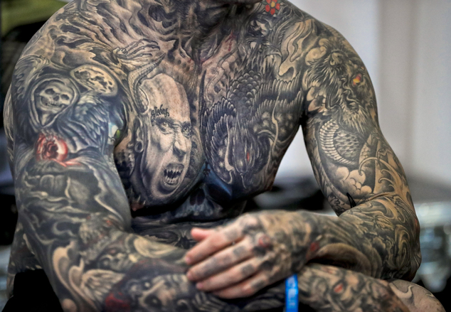 In this picture taken on Sunday, Oct. 16, 2016, well-known tattoo collector Yall Quinones, from Puerto Rico, shows off his tattoos during the International Tattoo Convention Bucharest 2016 in Bucharest, Romania. (AP Photo/Vadim Ghirda)