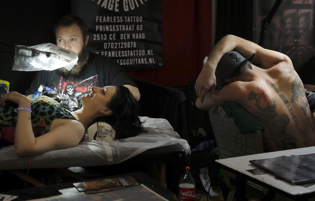 In this picture taken on Sunday, Oct. 16, 2016, people get tattoos during the International Tattoo Convention Bucharest 2016 in Bucharest, Romania. More than 100 tattoo and piercing artists brought their skills and art to a three-day convention in the Romanian capital.(AP Photo/Vadim Ghirda)