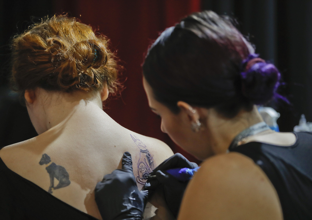 In this picture taken on Sunday, Oct. 16, 2016, a woman gets a tattoo during the International Tattoo Convention Bucharest 2016 in Bucharest, Romania. More than 100 tattoo and piercing artists brought their skills and art to a three-day convention in the Romanian capital.(AP Photo/Vadim Ghirda)