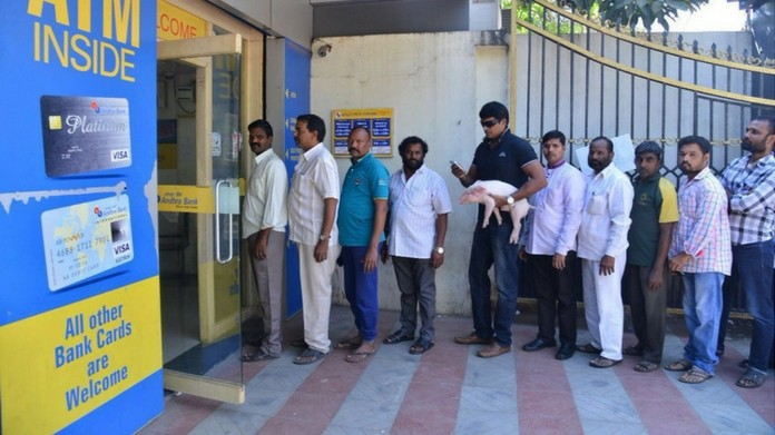 Actor Ravi Babu Spotted Holding A PigletIn A Bank Queue