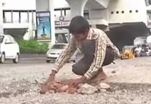 boy fill road potholes