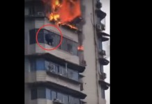 man hangs off building to escape fire