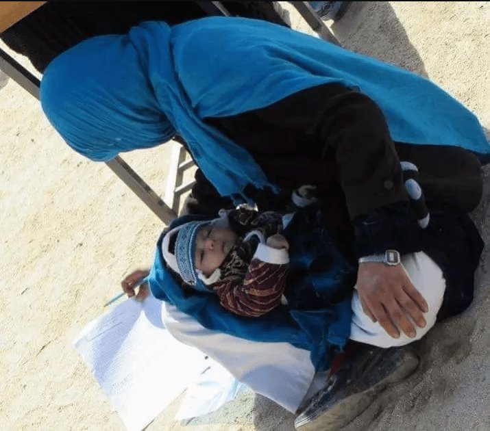 photo Of Afghan Woman Cradling Her Baby While Writing Exam Is Going Viral
