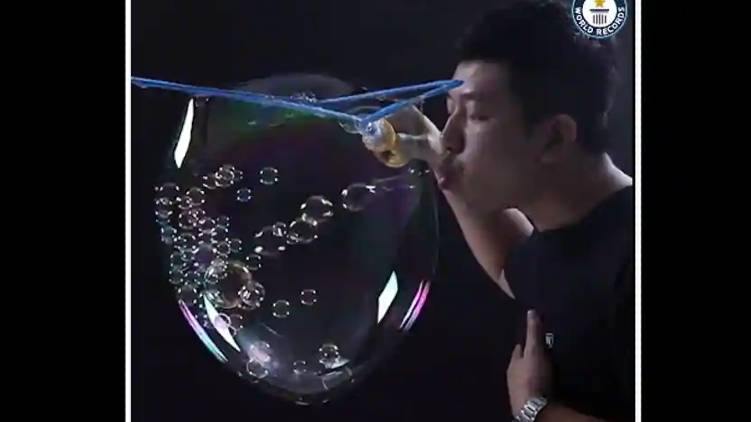 Man blows 783 small bubbles inside a big one