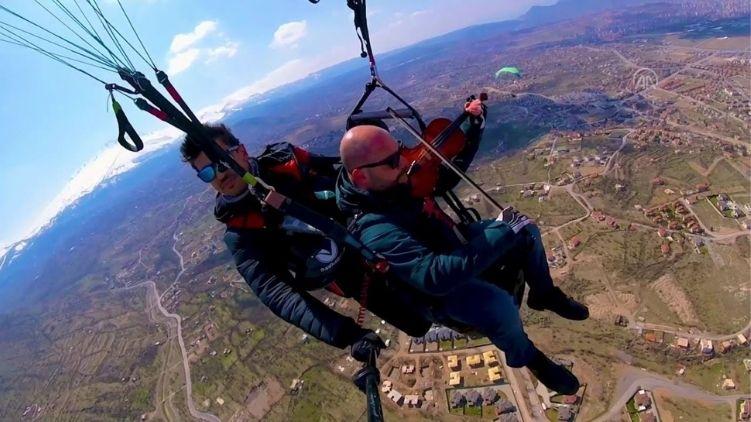 Man plays violin while paragliding